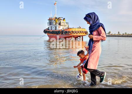 Bandar Abbas, Iran, Province Hormozgan - 16 avril, 2017: une femme dans un hijab à la tête d'un petit garçon par la main, promenades à travers les eaux peu profondes de la Pe