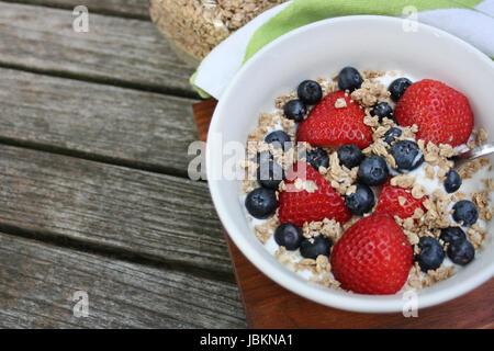 Petit-déjeuner sain bol. Dans un bol de granola blanc avec du yaourt grec et de baies sur fond de bois Banque D'Images