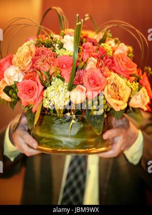 Homme portant vase avec fleurs. Visage masqué. Banque D'Images