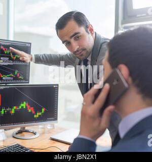 Les stocks commerciaux d'affaires en ligne. Les courtiers en regardant des graphiques, des index et des chiffres Banque D'Images