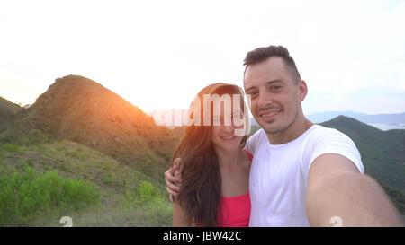 Couple, riant et selfies go round dans les montagnes de l'antenne avec de belles vue sur la ville au coucher du Banque D'Images