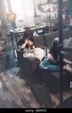 Jeune homme barbu ivre avec une bouteille de dormir sur un canapé après partie Banque D'Images