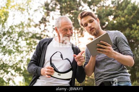 Jeune homme et son père senior avec lunettes VR à l'extérieur. Banque D'Images