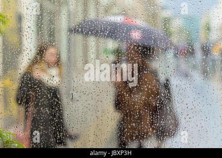 Silhouettes floues abstrait de personnes avec des parasols sur jour de pluie dans la ville, deux jeunes filles vu Banque D'Images