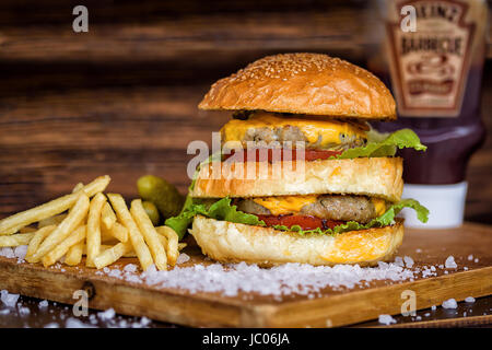 Maxi Burger fait maison avec pavé de boeuf grillé, salade, fromage, tomate, oignons, sauce barbecue, moutarde au Banque D'Images