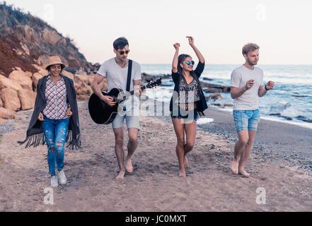 Groupe de jeunes et joyeux amis walking on beach Banque D'Images