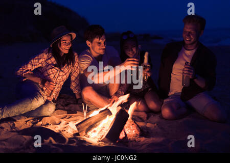 Amis assis sur la plage près de clink glasses bonfire Banque D'Images