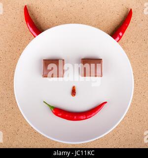 Piment du visage souriant avec les yeux chocolat sur plaque, sur fond de bois. Banque D'Images