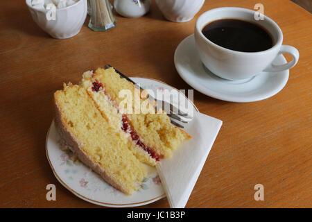 Tranche d'un gâteau éponge Victoria (yellow cake avec de la confiture et du givrage) et une tasse de café sur la Banque D'Images