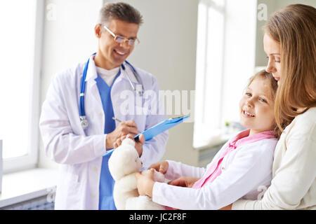Jeune fille souriante et sa mère médecin de passage dans les cliniques Banque D'Images