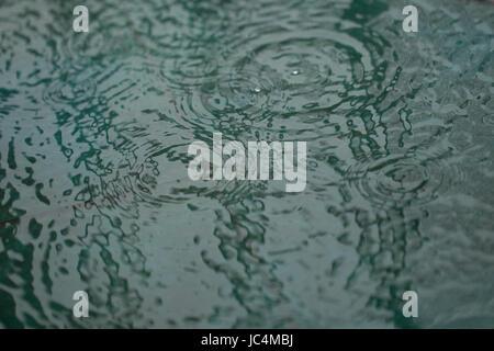 Chute de pluie ondulation sur une petite piscine d'eau. Résumé, la texture, l'arrière-plan. Sur les bords flous Banque D'Images