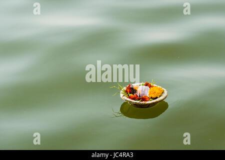 Un deepak, offrant un peu de fleurs et des bougies sont la natation sur le fleuve saint Ganges à dashashwamedh ghat Banque D'Images