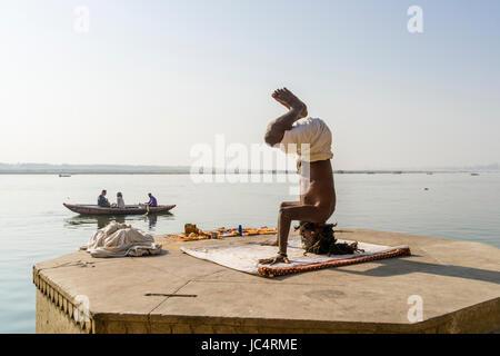 Un sadhu, saint homme, est la pratique du yoga asana sur une plate-forme à la sainte gange à meer ghat à la banlieue, Banque D'Images