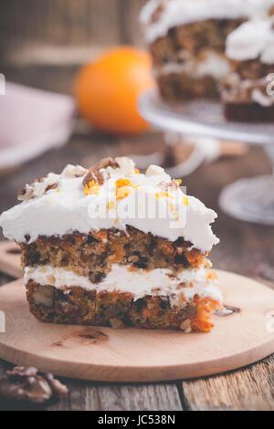 Gâteau aux carottes à la cannelle, noix et orange de fromage fondu sur table en bois rustique Banque D'Images