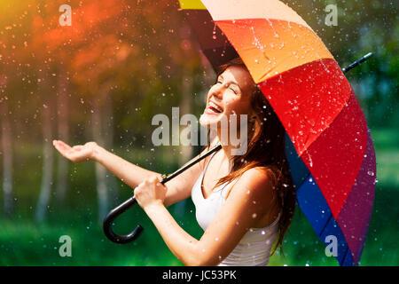 Laughing woman with umbrella contrôler pour la pluie Banque D'Images