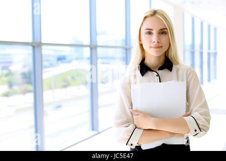 Femme d'affaires moderne heureux avec rapport financier est dans la salle de bureau Banque D'Images