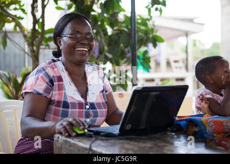 Une femme propriétaire de petite entreprise sur son ordinateur, Tanzania, Africa Banque D'Images