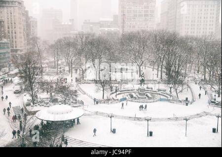 Scène d'hiver enneigé avec des pistes laissées par les piétons dans la neige dans l'Union Square comme un blizzard Banque D'Images