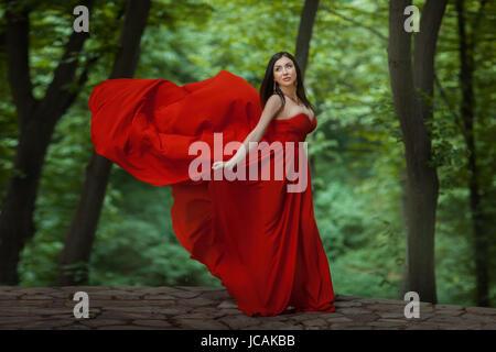 La fille est dans la forêt, sa robe rouge développe le vent. Elle se tient sur le précipice. Banque D'Images