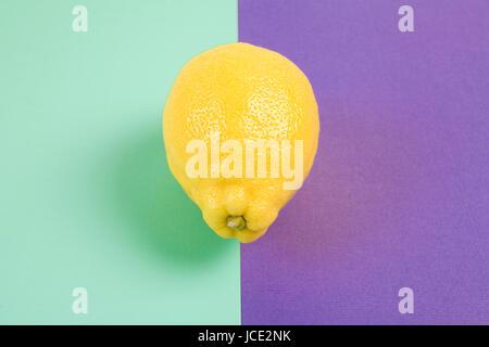 La photographie de la vie toujours minimal pop. pop citron isolés sur une photographie de la vie encore minime. Citron jaune isolé sur fond violet bicolor purpl Banque D'Images