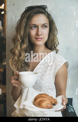 Jeune femme aux cheveux bouclés blonds wearing white dress sitting in cafe avec tasse de Cappuccino et de croissants, Banque D'Images