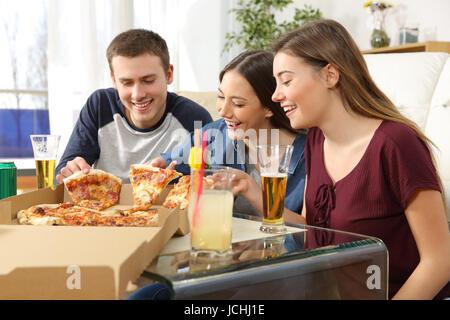 Trois amis parler et manger des pizzas assis sur le plancher de la salle de séjour à la maison Banque D'Images