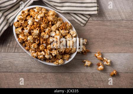 Opcorn caramel dans un bol sur la table en bois. Banque D'Images