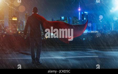 Businessman en costume et cape hero face à une victoire,tempête. concept cityscape background , scène de nuit . Banque D'Images