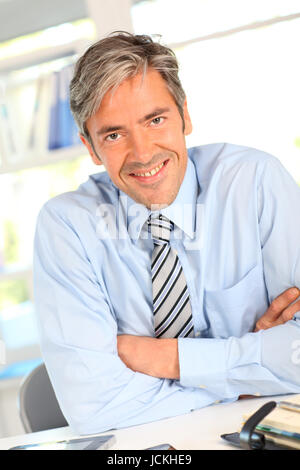 Smiling businessman in office with arms crossed Banque D'Images