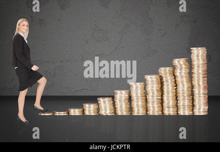 Portrait of confident young businesswoman climbing up pièces empilées en croissance Banque D'Images