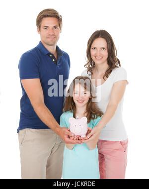 Portrait of happy family holding piggy bank ensemble sur fond blanc Banque D'Images