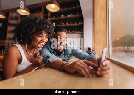 Jeune couple assis ensemble au café et prendre l'aide de selfies téléphone intelligent. Jeune homme et femme en Banque D'Images
