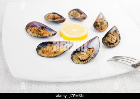 Les moules grillées au four, accompagné de tranches de citron râpé, le persil et pan. Les moules sur la plaque blanche. Banque D'Images