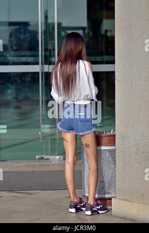 Young teen girl wearing denim shorts avec leg tattoo Banque D'Images