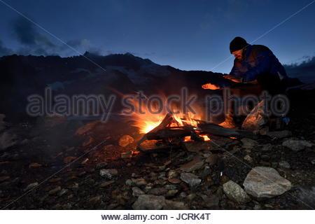Spéléologue italien Fulvio Iorio réchauffe ses mains près d'un feu juste après le coucher du soleil Banque D'Images