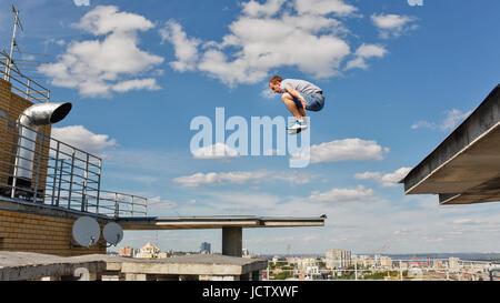 Un homme saute de toit en toit. Parkour. Mode de vie actif. Roofer Banque D'Images