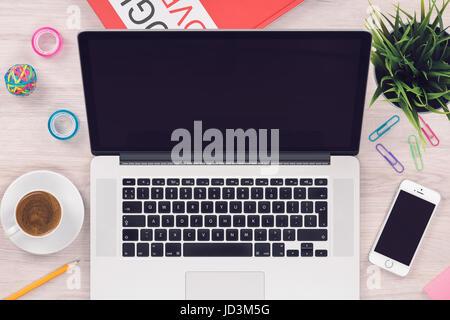 Vue de dessus de l'espace de mise à plat avec la maquette open laptop et smartphone sur un bureau en bois bureau Banque D'Images