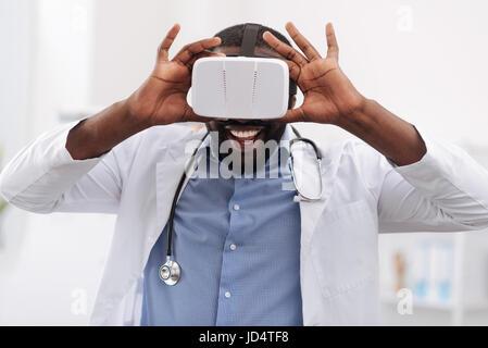 Cheerful heureux médecin à l'aide de lunettes de réalité virtuelle Banque D'Images