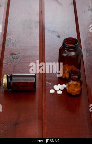 Les bouteilles de pilules brun et tas de pilules blanches sur la table en bois Banque D'Images