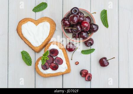 Bol rempli de cerises et biscuits en forme de coeur se propager avec quark, cerises et une brindille de menthe Banque D'Images