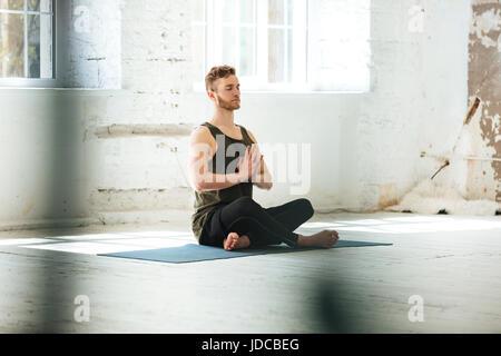 Candide jeune homme assis sur un tapis de fitness et méditer dans la salle de sport Banque D'Images