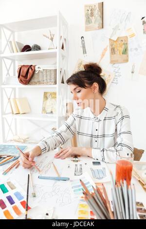 Portrait d'une belle jeune femme designer de mode travaillant en atelier
