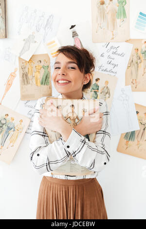 Jolie jeune femme fahion tenant son sketchbook designer in studio