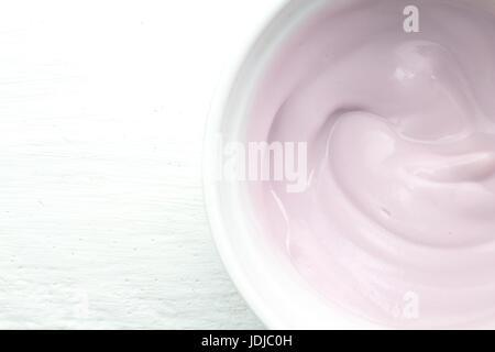 Naturellement crémeux framboise yogourt aux fruits colorés en blanc bol en verre sur la table en bois blanc close Banque D'Images