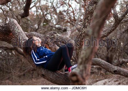 Une adolescente se trouve dans le creux d'un grand chêne sur Ocracoke Island, Caroline du Nord. Banque D'Images