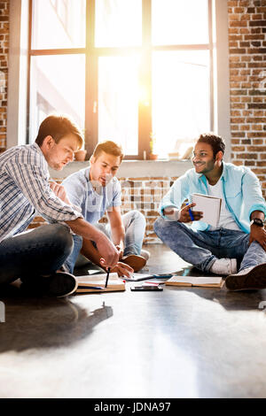 Groupe de jeunes professionnels qui travaillent sur de nouveaux projets d'affaires en bureau de petite entreprise, Banque D'Images