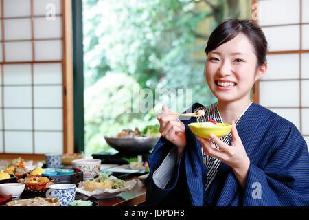 Femme portant un yukata japonais manger au ryokan traditionnel, Tokyo, Japon Banque D'Images
