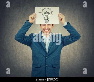 Smiling businessman holding enseignant ou un livre blanc au-dessus de sa tête avec une ampoule de croquis. La science et l'idée d'entreprise concept isolé sur gray backg