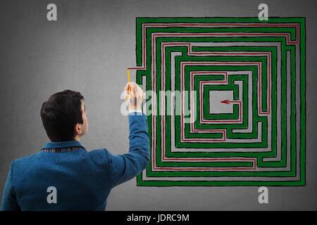 Young businessman holding un crayon dans sa main essayer de trouver la solution d'un labyrinthe carré d'imagination, le dessin d'une ligne rouge à la réussite. Rectangle labyrin