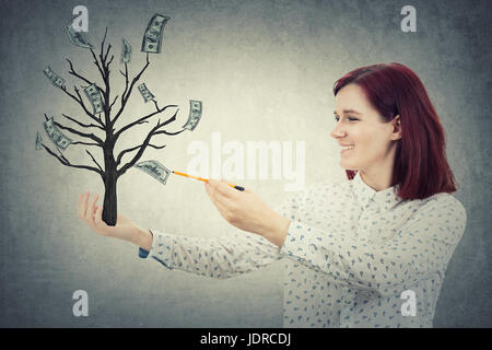Young smiling girl avec un crayon à la main, croquis dessin d'un arbre magique avec de plus en plus de dollars sur Banque D'Images